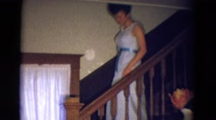 1969: a young woman walking down a staircase, perhaps in her prom dress DILLER Stock Footage