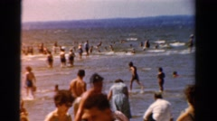 1954: many people are recreating in the shallow water of the beach. OHIO Stock Footage