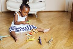 Little cute african american girl playing with animal toys at home, pretty Stock Photos