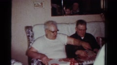 1954: family celebrating birthday of a grandfather he is unwrapping his present Stock Footage