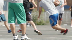Man in a sport clothes stands near a court when other players play streetball Stock Footage