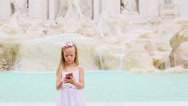 Adorable little girl with smart phone at warm day outdoors in european city near Stock Footage