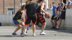 Young girl attacks and throws a ball into a basket in a streetbal (slow motion) Stock Footage