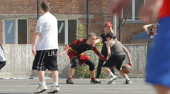Young girls watch for young men playing streetball in outdoors (slow motion) Stock Footage