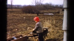 1954: a child in an orange hat playing outdoor with a wheelbarrel OHIO Stock Footage