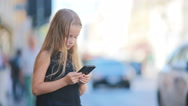 Adorable little girl with smart phone at warm day outdoors in european city Stock Footage