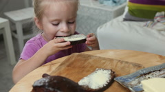 Pretty little girl eating butter from sandwich Stock Footage