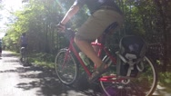 People riding bikes through a beautiful green forest Stock Footage