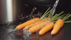 SLOW MOTION: Water stream falls on a carrots on a table in a kitchen Stock Footage