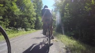 People riding bikes through beautiful green forest Stock Footage
