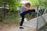 Blond woman middle aged stretching legs in a park Stock Photos