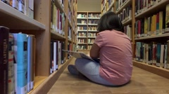 Young girl reads a comic sitting on the floor of a library Stock Footage