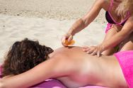 Woman applying sun cream on woman's back while in holidays Stock Photos