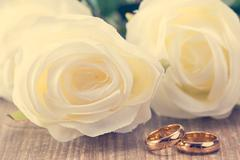 Wedding rings with white roses Stock Photos