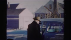 1956: a man gets into his car and moves the car toward a large garage and parks Stock Footage