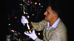 1956: a man wearing white gloves inspecting a bottle in front of a christmas Stock Footage