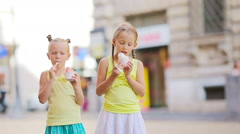 Adorable little girls eating ice-cream outdoors at summer. Cute kids enjoying Stock Footage