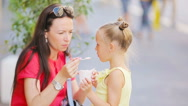 Young mother and her daughters eating ice cream outdoors. Mum feeds his daughter Stock Footage