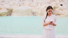 Young woman with smart phone near famous Fontana di Trevi Stock Footage