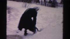 1956: a woman wearing a black coat and a scarf is vigorously shoveling snow  Stock Footage