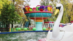 A spinning carousel and artificial swan on the water Stock Footage