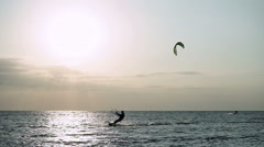 Kitesurfing. Dark silhouettes of surfers riding on boards on Azov sea at dusk HD Stock Footage