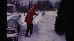 1956: a man dressed with very warm clothes shoveling abundant snow  Stock Footage