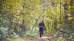 Young runner girl have jogging on autumn road covered with fallen leaves. Sports Stock Footage