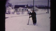 1956: man and woman shoveling snow in their neighborhood in front of their home Stock Footage