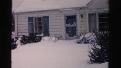 1956: a man shoveling snow outdoor one of many houses covered  Stock Footage