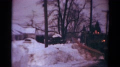 1954: a large snow plowing moving down the street clearing the snow in its path Stock Footage