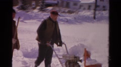 1954: two men removing snow by using a snowblower and shovel. NEW YORK Stock Footage