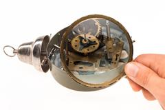 The male hand with magnifier and clockwork Stock Photos