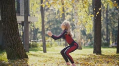 Sexy Attractive female blonde bikini-fitness model stretching in the autumn park Stock Footage
