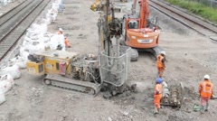 Construction workers on site next to a section of railway track. Stock Footage
