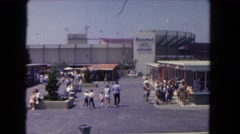 1962: people walking through a parking lot towards a large outdoor stadium  Stock Footage