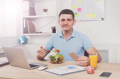 Man has healthy business lunch in modern office interior Stock Photos