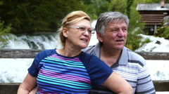 Middle-aged couple enjoys near the swollen river. Stock Footage