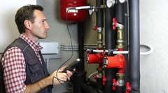 Plumber working measures the temperature in a thermal power Stock Footage