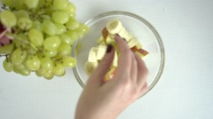 Putting grapes into fruit salad Stock Footage