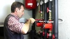 Plumber at work installing a circulation pump Stock Footage