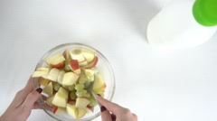 Beautiful girl hands mixing fruit salad in a glass bowl Stock Footage