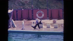1962: black seals are being trained by a man in white dress SAN PEDRO Stock Footage