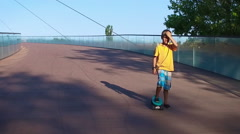 Child cruising on a pennyboard, slow motion Stock Footage
