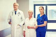 Medics and senior patient woman at hospital Stock Photos