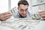 Happy businessman with heap of money in office Stock Photos