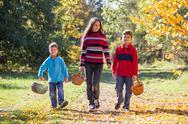 Three kids walking on autumn forest with baskets Stock Photos