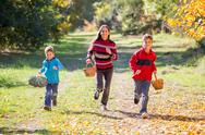 Three kids running on autumn forest with baskets Stock Photos