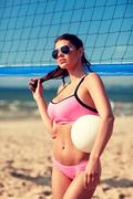 Young woman with volleyball ball and net on beach Kuvituskuvat
