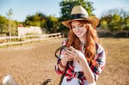 Smiling cowgirl using mobile phone while standing at ranch fence Stock Photos